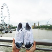 Custom, hand painted London Skyline Vans featuring the Big Ben, London eye, and other building silhouettes visible in the London Skyline. Displayed in front of the London Eye and Big Ben on a bridge in London.