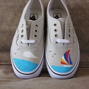 Custom, hand painted Sailboat Vans shoes featuring a sailboat, seagulls, and a cloud over the sea.