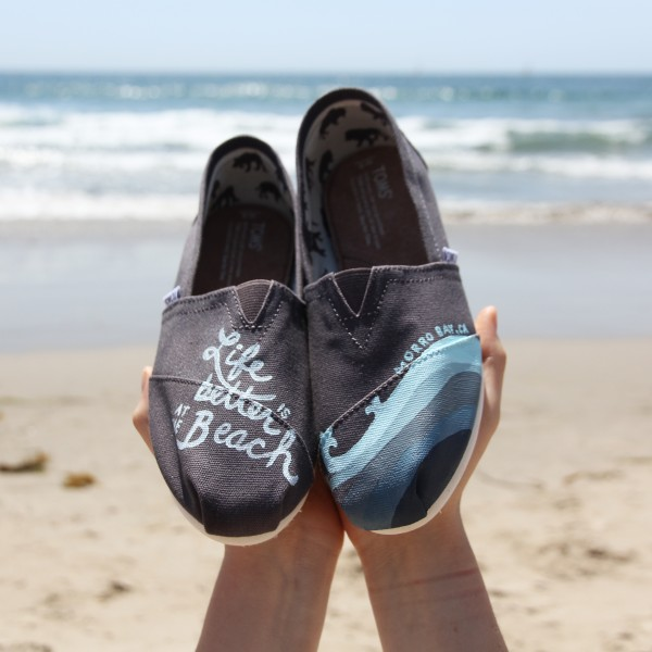 Custom, hand painted Life is Better at the Beach TOMS shoes featuring lettering and a gradient wave pattern. Displayed at Santa Monica Beach in California.