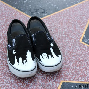 Custom, hand painted LA Cityscape Vans shoes featuring building silhouettes visible in the Los Angeles Skyline. Displayed at the Hall of Fame walk of stars in Hollywood.