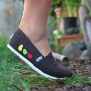 Custom, hand painted Fruits TOMS shoes featuring a green apple, a red apple, and a golden pear on either side.