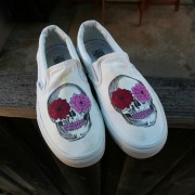 Custom, hand painted Floral Skull Vans slip on shoes featuring detailed illustrated skulls with flowers and pink teeth.