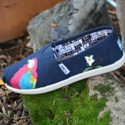 Custom, hand painted Rainforest youth TOMS shoes featuring a scarlet macaw parrot and a lemur in a tropical rainforest.