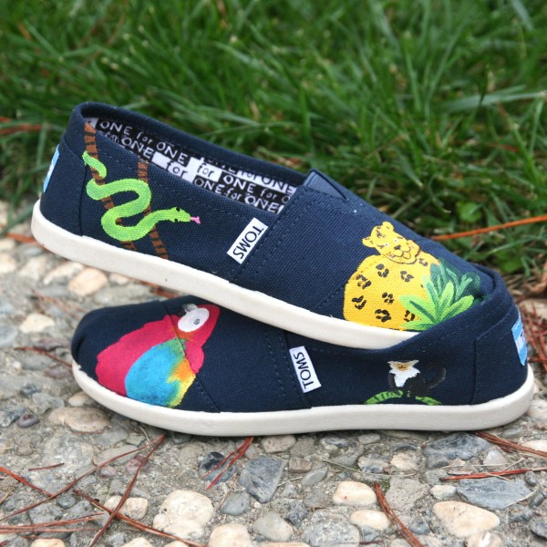 Custom, hand painted Rainforest youth TOMS shoes featuring a scarlet macaw parrot, lemur, jaguar, and snake in a tropical rainforest.