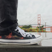 Custom, hand painted East Coast vs. West Coast Converse shoes featuring the Golden Gate Bridge from San Francisco, California in front of the actual Golden Gate Bridge in San Francisco, CA.