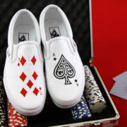 Custom, hand painted poker card vans displayed on a game table with poker chips.